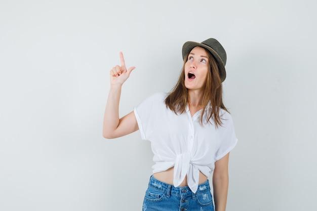 Giovane donna in t-shirt, jeans, cappello rivolto verso l'alto e guardando stupito, vista frontale.