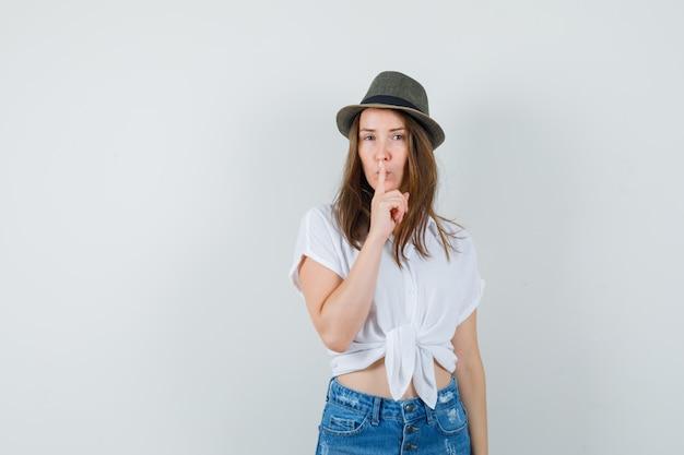 Giovane donna in t-shirt, jeans, cappello che mostra gesto di silenzio e guardando attento, vista frontale.