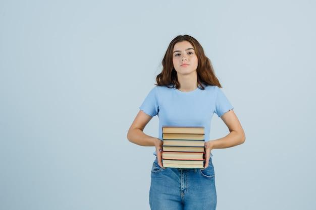 Giovane signora in maglietta, jeans che tengono i libri e che sembra fresca, vista frontale.