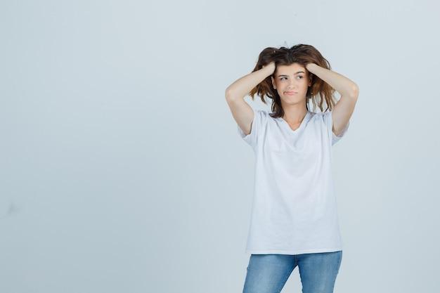 Giovane donna in t-shirt, jeans che tengono le mani sulla testa e guardando smemorato, vista frontale.