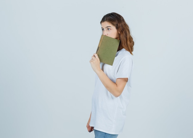 Young lady in t-shirt, jeans leaning book on mouth and looking thoughtful , front view.