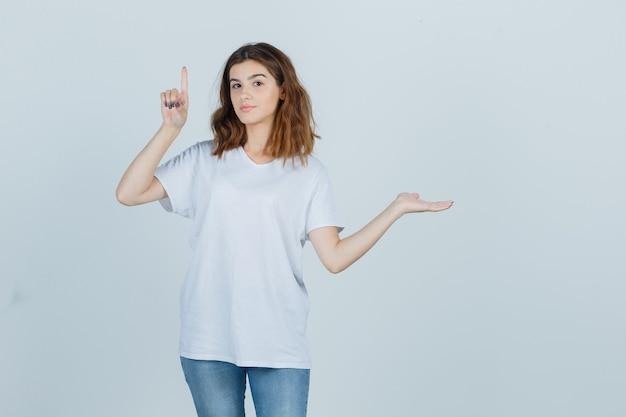 Giovane donna in t-shirt, jeans rivolti verso l'alto mentre mostra qualcosa e sembra sicura, vista frontale.