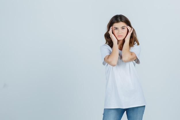 Giovane donna in t-shirt, jeans strofinando le tempie e guardando affaticato, vista frontale.