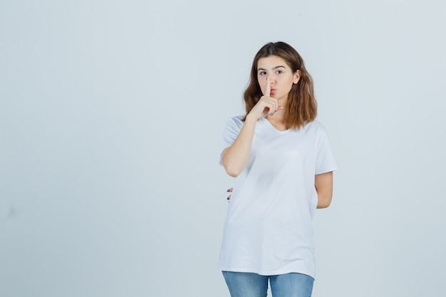 Young lady in t-shirt, jeans showing silence gesture and looking serious , front view.