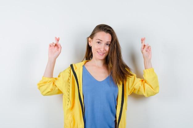 Giovane donna in maglietta che tiene le dita incrociate e sembra speranzosa, vista frontale.