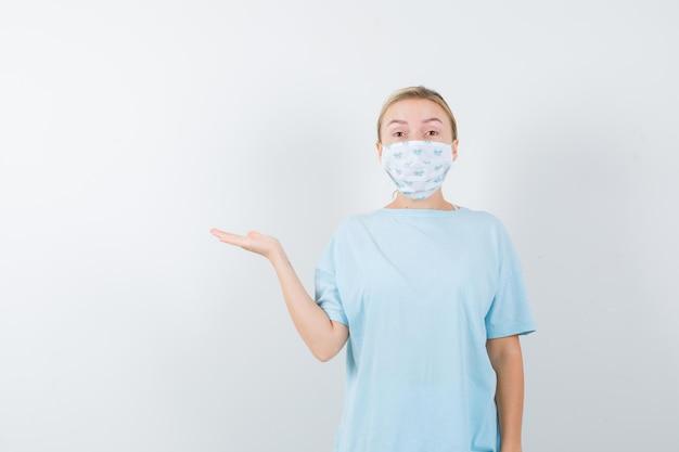 Giovane donna in maglietta, maschera che fa un gesto di benvenuto e sembra eccitata looking