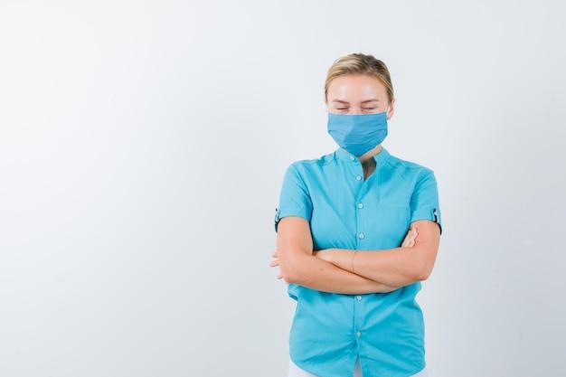 Giovane donna in t-shirt, maschera in piedi con le braccia incrociate e con aria risentita