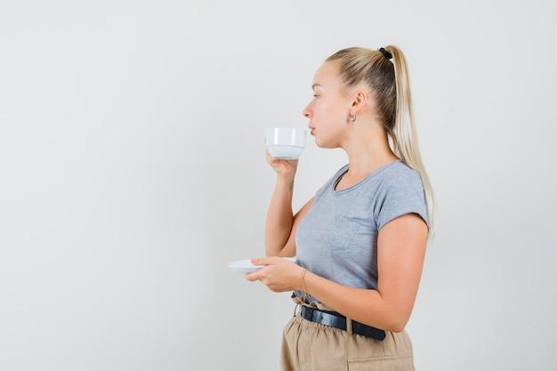 Giovane donna in maglietta e pantaloni che bevono tè mentre distoglie lo sguardo e sembra pensierosa