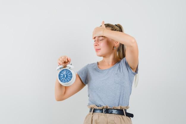 Giovane donna in maglietta e pantaloni che tengono sveglia e che sembra smemorato