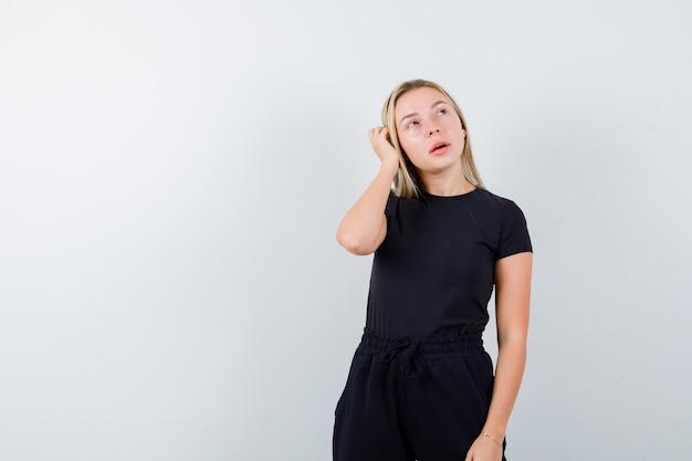 Giovane donna in t-shirt, pantaloni tenendo la mano sulla testa e guardando pensieroso, vista frontale.