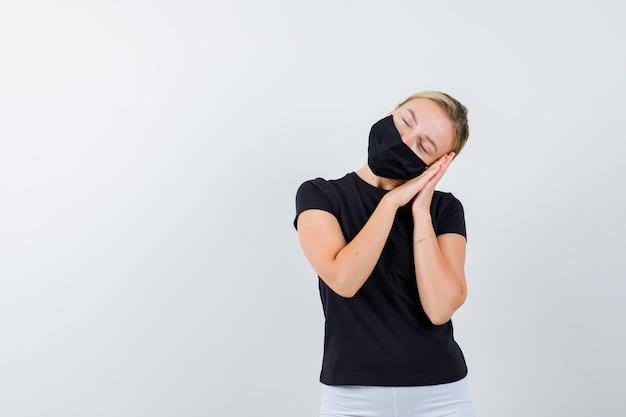 Giovane donna in t-shirt, pantaloni, maschera medica che imbottisce il viso sulle mani isolate