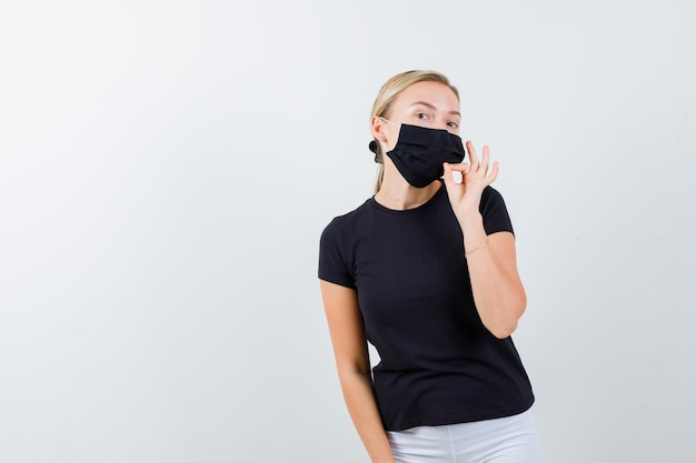 Young lady in t-shirt, pants, medical mask showing zip gesture and looking serious