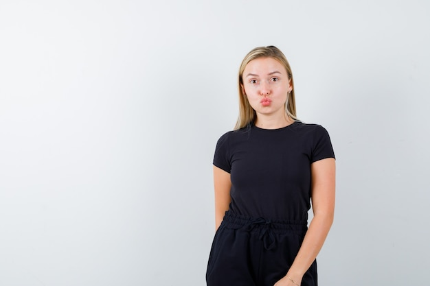 Young lady in t-shirt, pants sending kiss with pouted lips and looking pretty , front view.