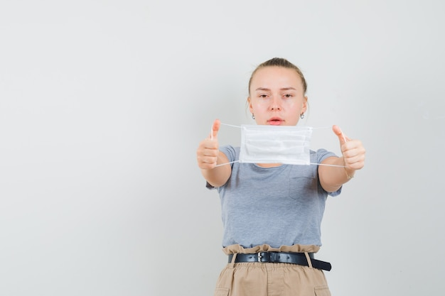 Giovane donna in maglietta e pantaloni che mostrano mascherina medica e guardando attenti