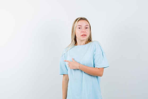 Young lady in t-shirt pointing to the left side and looking confident , front view.