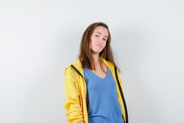 Giovane donna in t-shirt in posa mentre guarda la macchina fotografica e sembra carina, vista frontale.