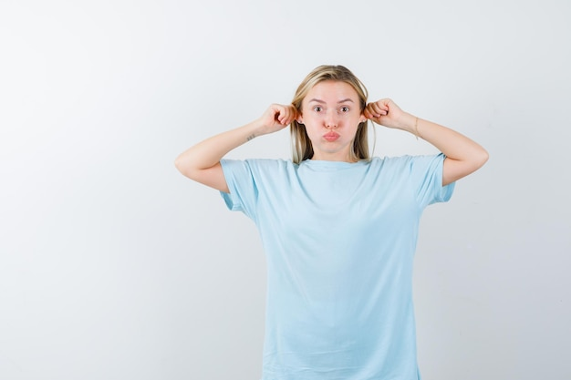 Giovane donna in maglietta che tira i lobi delle orecchie mentre soffia sulle guance e sembra carina isolata