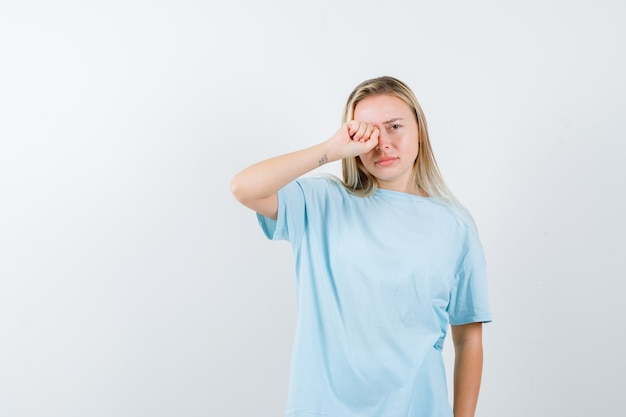 Young lady in t-shirt rubbing eye and looking offended , front view.