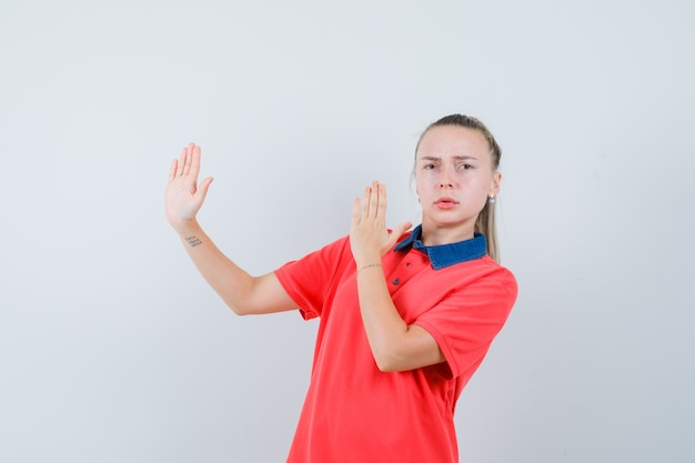 Young lady in t-shirt showing karate chop gesture and looking strict