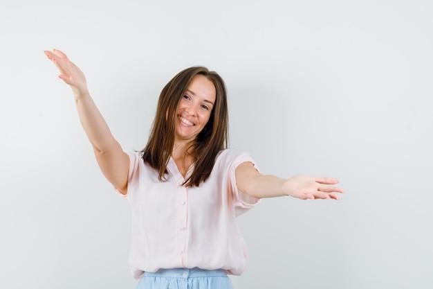 Giovane donna in t-shirt, gonna che apre le braccia per abbraccio e sembra amichevole, vista frontale.