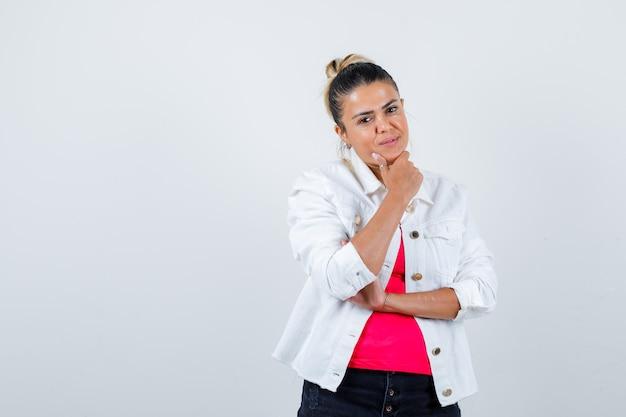 Giovane donna in t-shirt, giacca bianca con la mano sul mento e sguardo soddisfatto, vista frontale.