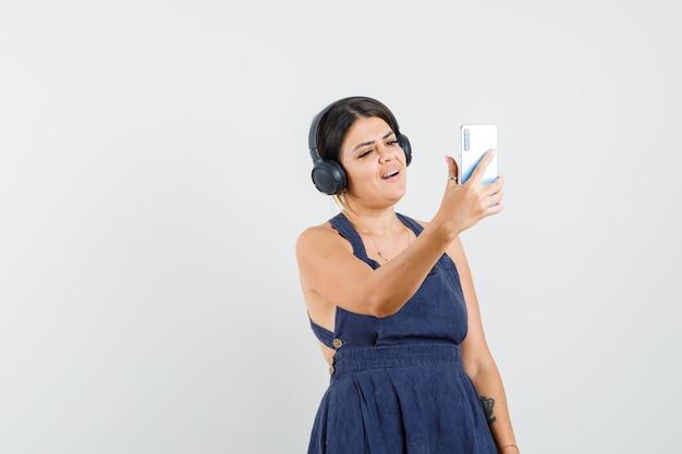 セルフィーを撮り、ドレスを着てヘッドフォンで音楽を楽しんで、陽気に見える若い女性