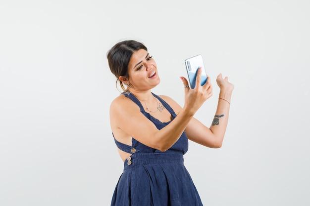 Молодая леди, делающая селфи на мобильном телефоне в платье и выглядящая веселой