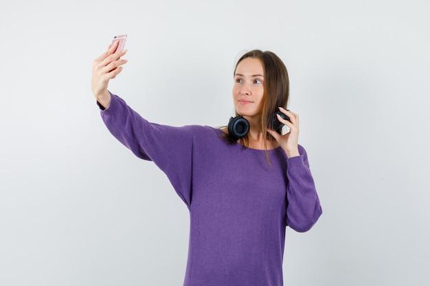 紫のシャツ、正面図でヘッドフォンを保持しながら自分撮りを取っている若い女性。