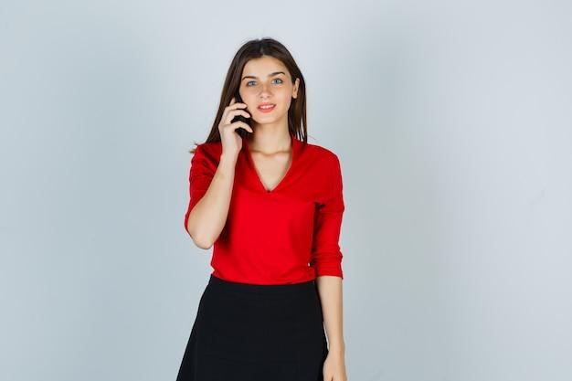 Giovane signora che parla sul telefono cellulare in camicetta rossa, gonna e che sembra felice