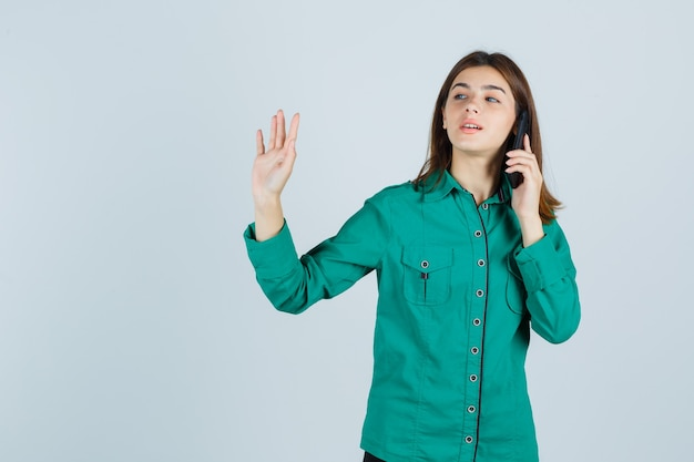 Young lady talking on mobile phone, showing stop gesture in green shirt and looking confident. front view.