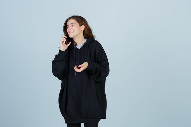 特大のパーカー、ズボンで携帯電話で話し、うれしそうに見える若い女性。正面図。