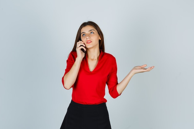 빨간 블라우스, 치마에 휴대 전화로 이야기하고 사려 깊은 찾고 젊은 아가씨