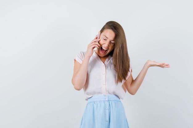 Tシャツ、スカート、嬉しそうに携帯電話で話している若い女性。正面図。