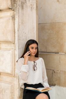 Молодая леди разговаривает по телефону, держа книгу