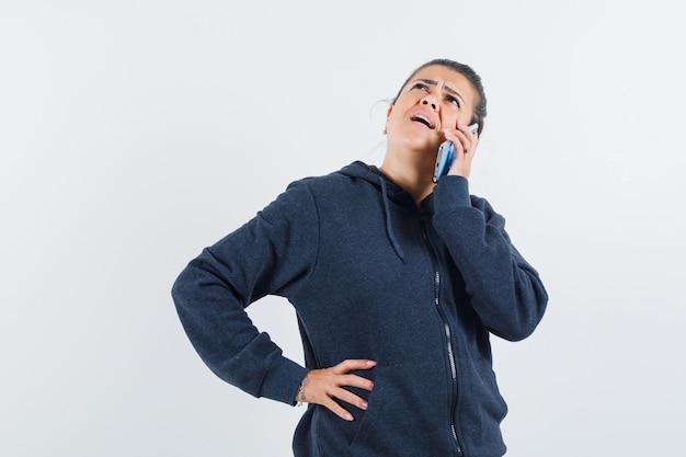 Молодая дама разговаривает по телефону, держась за талию в куртке и выглядит разговорчивой