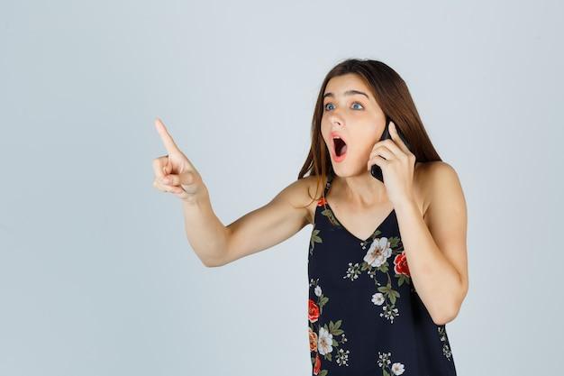 스마트폰으로 이야기하는 젊은 여성이 블라우스를 입은 채 잠시 몸짓을 하고 놀란 표정을 짓고 있습니다. 전면보기.