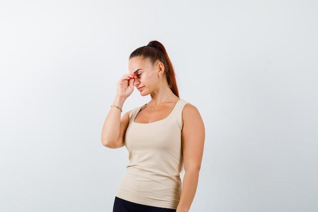 Giovane donna in canottiera strofinando naso e occhi e guardando affaticato, vista frontale.