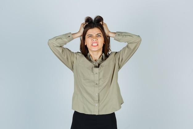 셔츠, 치마를 입고 이를 악물고 공격적인 정면을 바라보면서 손으로 머리카락을 찢는 젊은 여성.