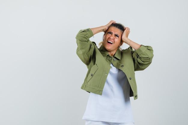 Молодая дама рвет волосы в шортах от футболки и выглядит встревоженной