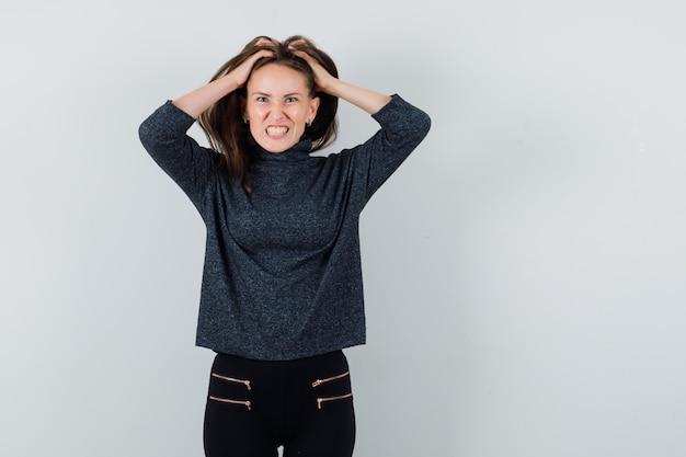 Giovane signora che si strappa i capelli in camicia