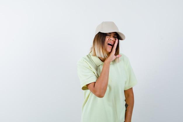 Tシャツ、キャップ、真剣に見える、正面図で手の後ろに秘密を語る若い女性。
