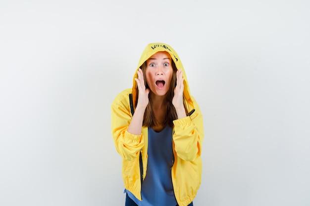 秘密を告げる、またはtシャツ、ジャケットで何かを発表し、興奮している若い女性