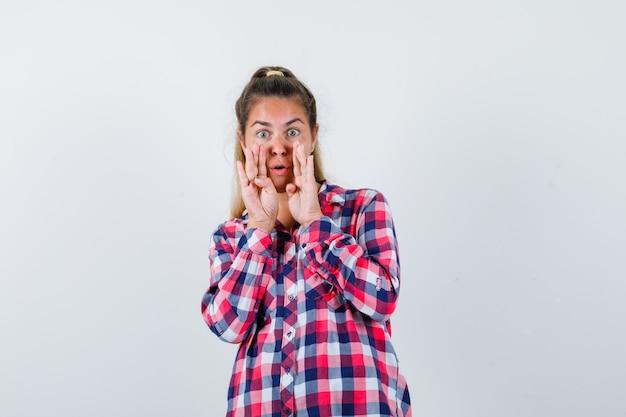 Молодая леди рассказывает секрет с руками возле рта в клетчатой рубашке и выглядит взволнованной. передний план.