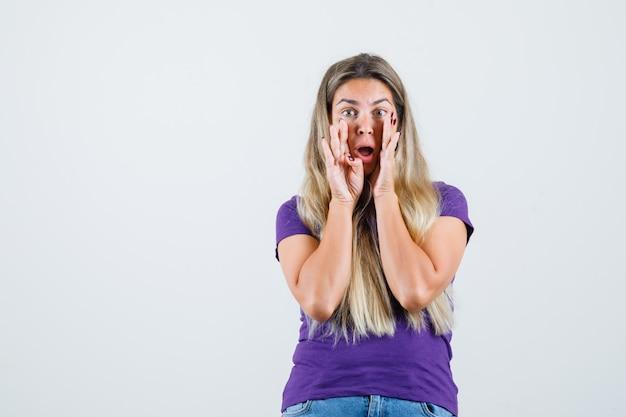 紫のtシャツ、ジーンズの正面図で口の近くの手で秘密を語る若い女性。