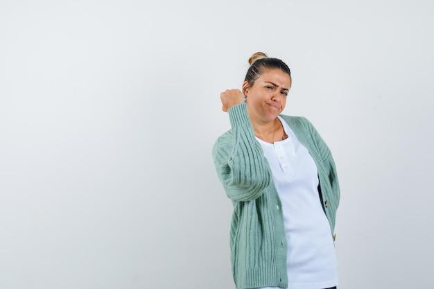 Giovane donna che minaccia di pugno in maglietta, giacca e sembra sicura