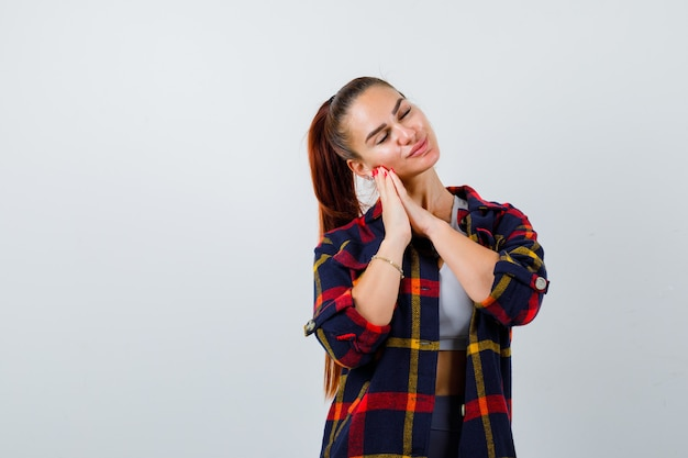 Young lady in top, plaid shirt leaning on hands as pillow and looking sleepy , front view.