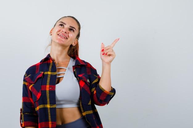 Giovane donna in alto, camicia a quadri che punta all'angolo in alto a destra e sembra allegra, vista frontale.