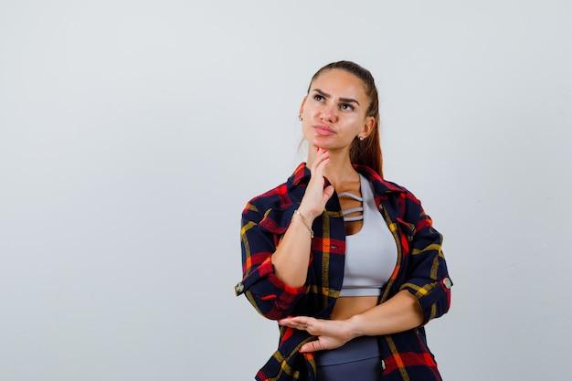 Giovane donna in alto, camicia a quadri con la mano sotto il mento e sguardo pensieroso, vista frontale.