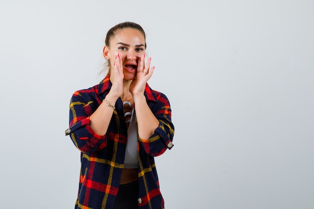 Young lady in top, plaid shirt with hands near mouth to tell secret and looking excited , front view.