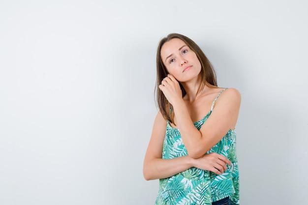 Giovane donna che si tocca la guancia, distoglie lo sguardo e sembra pensierosa. vista frontale.